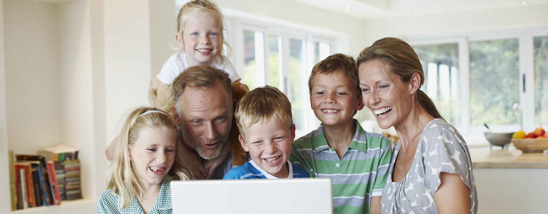 Familie sitzt gemeinsam vor einem Laptop