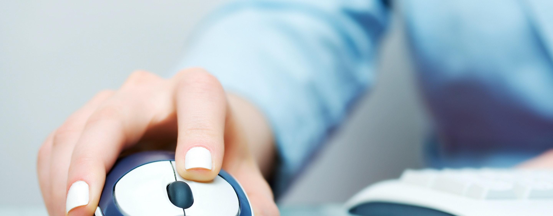 Frau arbeitet mit einer Maus am PC