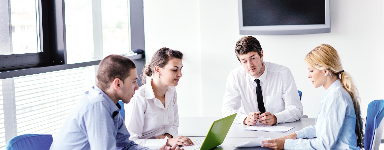 Gruppe junger Mitarbeiter sitzen in einer Besprechung